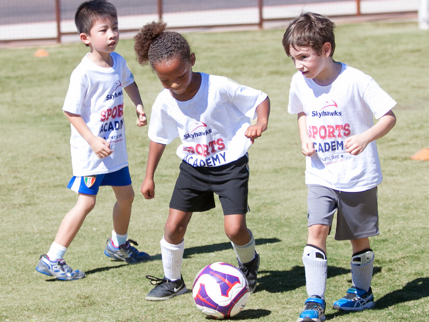 Girl-Dribbling-Ball-Between-Boys